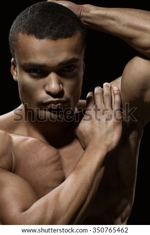 He is sculpting his own body. Closeup portrait of a well built African man posing on black background