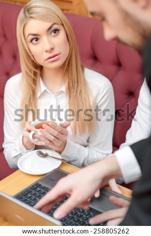 He is so confident. Top view image of beautiful woman in formalwear looking attentively at her male colleague while having lunch in the cafe  - stock photo