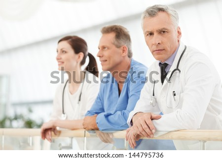 He is the most experienced and talented doctor. Confident mature doctors looking at camera while standing near his colleagues - stock photo