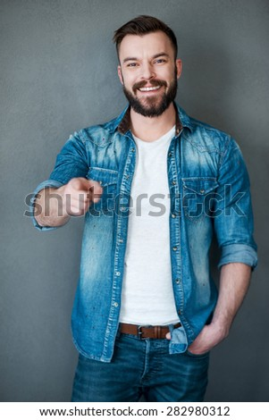 He knows what he wants!Cheerful young man pointing you and smiling at camera while standing against grey background - stock photo