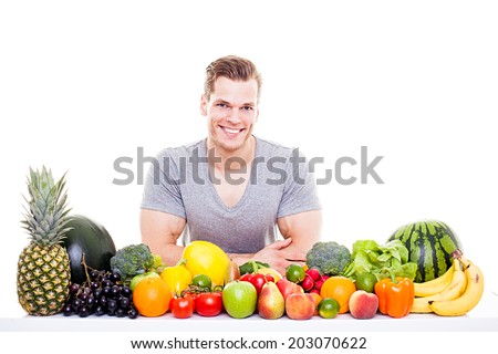 He knows what's good for you! - Handsome muscular man sitting behind a row of fruits and vegetables, isolated on white background - stock photo