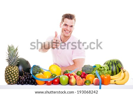 He knows what's good for you! - Handsome muscular man sitting behind a table full of vegetables and fruits and showing thumb up, isolated on white - stock photo