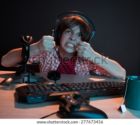 He like play and win video games. In blue light of display emotional kid play computer games online. - stock photo