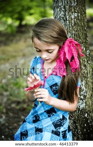 He loves me, he loves me not - little girl pulling flower petals outdoors. - stock photo