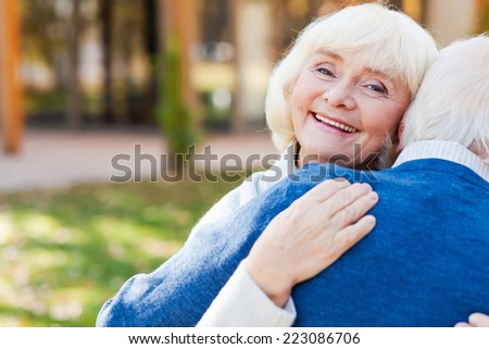 He makes me happy. Happy senior woman embracing her husband and smiling while both standing outdoors - stock photo