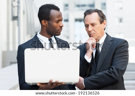 He needs an expert advice. Two confident business men looking at laptop while one of them holding hand on chin - stock photo