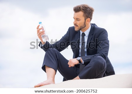 He needs to get refreshed. Depressed young businessman holding bottle with water and looking at it while sitting on sand  - stock photo
