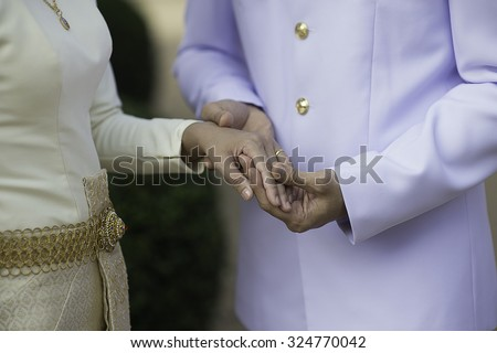 He Put the Wedding Ring on He, Thai Suit - stock photo
