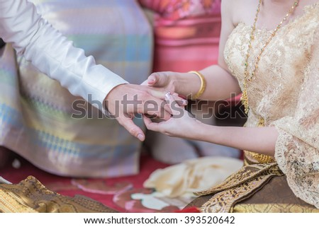 He Put the Wedding Ring on Her in the marriage ceremony In Asia, Thailand - stock photo
