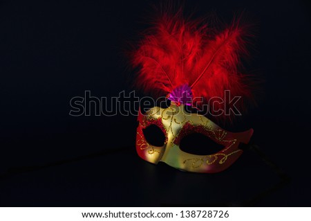 he/she chewed of golden carnival with red feathers on dark bottom - stock photo