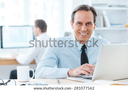 He thrives in this work. Happy businessman in formalwear working on laptop and smiling at camera while sitting at his desk in office - stock photo