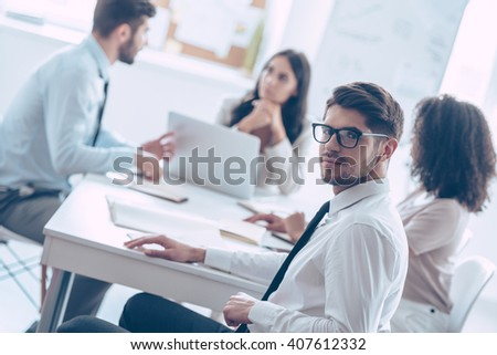 He trusts his business team. Handsome young man in glasses looking at camera while sitting at the office table with his coworkers - stock photo