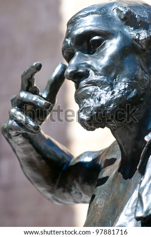 Head and arm of the bronze statue Jaques de Wissant, 1888 by Rodin displayed in Murcia, Spain, in the open air with blue reflections from the blue sky  The Thinker. - stock photo