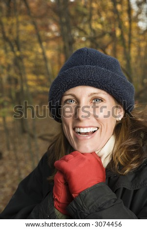 Head and shoulder portrait of smiling Caucasian woman in hat and gloves in woods. - stock photo