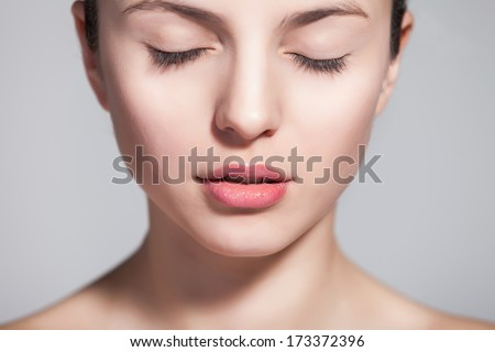 Head and shoulder shot of a beautiful young woman in the nude with eyes closed over gray background - stock photo
