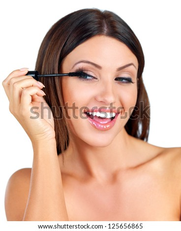 Head and shoulders beauty portrait of a happy naked woman with a beautiful smile applying mascara with a brush to her long eye lashes isolated on white