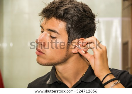 Head and Shoulders Close Up of Young Attractive Man with Dark Hair, Grooming Himself - Cleaning Ear Wax from Ears Using Cotton Swab Stick, in Bathroom at Home - stock photo