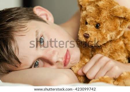 Head and Shoulders Close Up of Young Teenage Boy Lying on Bed and Snuggling with Soft Brown Teddy Bear and Staring at Camera with Sad or Serious Expression - stock photo