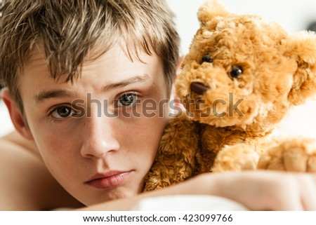 Head and Shoulders Close Up of Young Teenage Boy Lying on Bed and Snuggling with Soft Brown Teddy Bear and Staring at Camera with Worried Expression - stock photo