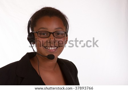 Head and shoulders of a young African American business woman wearing headset over white - stock photo