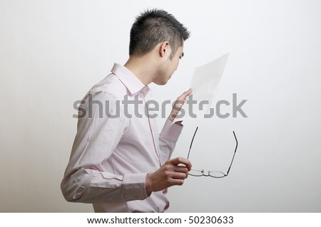 Head and shoulders of an Asian man looking at a letter that has been left blank.