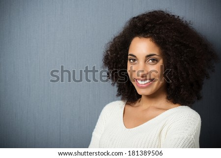 Head and shoulders portrait of a beautiful friendly African American woman with a curly afro hairstyle looking at the camera with a lovely smile, with copyspace - stock photo
