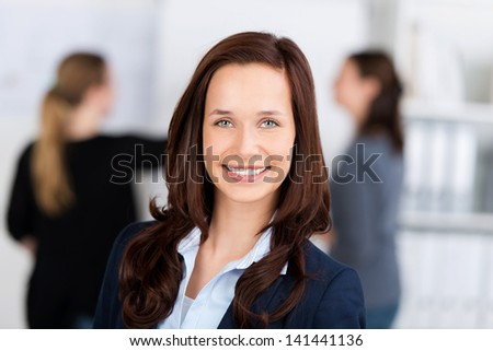 Head and shoulders portrait of a beautiful smiling businesswoman looking at the camera with two blurred colleagues in the background - stock photo