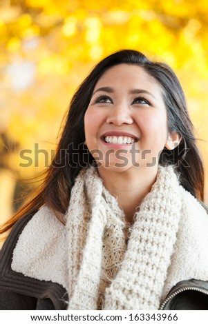 Head and shoulders portrait of a mid 20s Asian woman outside in the fall under yellow autumn leaves - stock photo