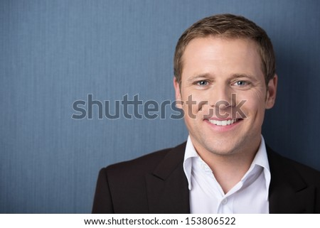 Head and shoulders portrait of a young friendly smiling business man looking at the camera against a blue background with copyspace - stock photo