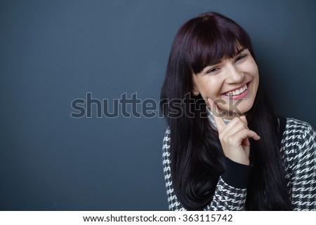 Head and Shoulders Portrait of Cheerful Young Woman Wearing Black and White Patterned Jacket with Hand Resting on Chin in Studio with Navy Blue Background and Copy Space - stock photo