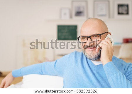 Head and Shoulders Portrait of Mature Man with Gray Facial Hair Wearing Eyeglasses and Casual Blue Shirt Smiling While on Cell Phone in Living Room on Relaxing Day at Home, Copy Space to Left of Image - stock photo