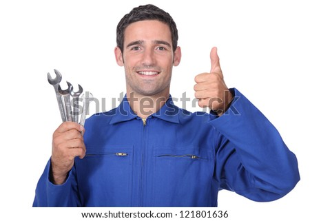 head and shoulders portrait of plumber holding wrenches all smiles - stock photo