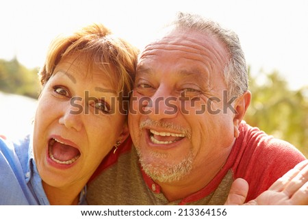 Head and Shoulders Portrait Of Senior Couple In Garden