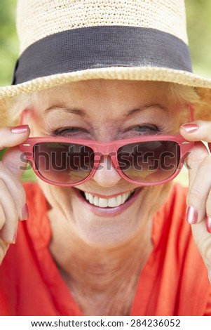 Head And Shoulders Portrait Of Smiling Senior Woman Wearing Sunglasses - stock photo