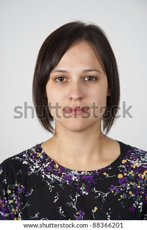 Head and shoulders shot of a young caucasian woman looking straight at the camera with a very neutral look - stock photo