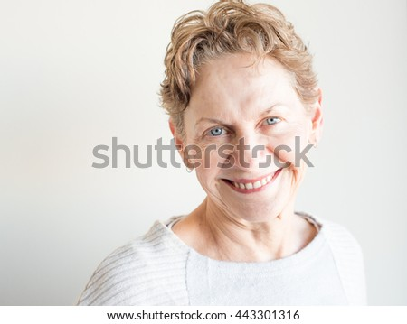 Head and shoulders view of older woman in cream top smiling against neutral background - stock photo