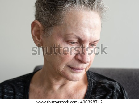 Head and shoulders view of older woman with grey hair looking sad and tired (selective focus)