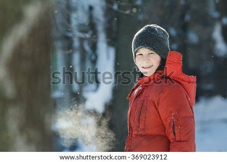 Head and shoulders winter outdoor portrait of cheerful teenage boy breathing with visible steam mouth in frosty sunny day - stock photo