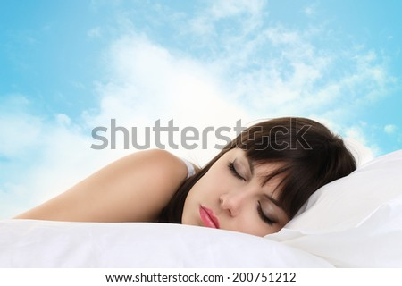 head girl sleeping on pillow with blue sky in background - stock photo