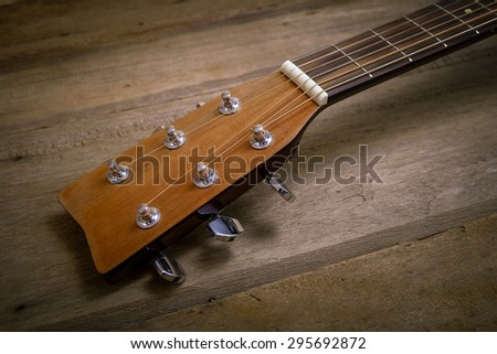 Head guitar on wood background, vintage tone - stock photo