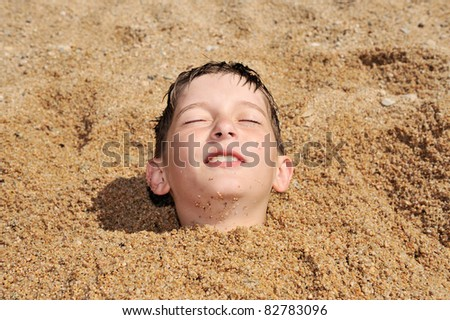 head of a boy buried in the sand - stock photo