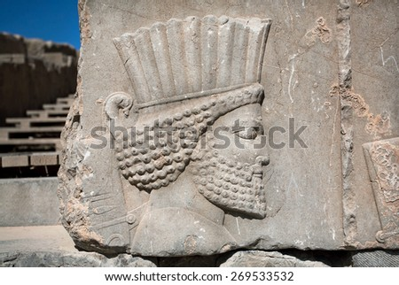 Head of ancient warrior on the destroyed stone bas-relief in famous city Persepolis, Fars Province, Iran. Persepolis was a capital of the Achaemenid Empire (550 - 330 BC).  - stock photo