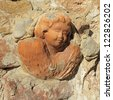 head of angel in tuscan terracotta  on antique stone wall in Tuscany, Italy, Europe - stock photo