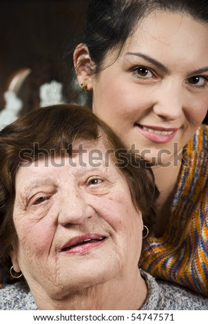 Head of beautiful two  generation grandmother and granddaughter standing in a hug and smiling - stock photo