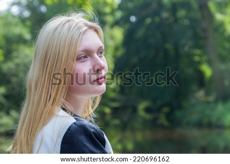 Head of blond girl with water and green trees