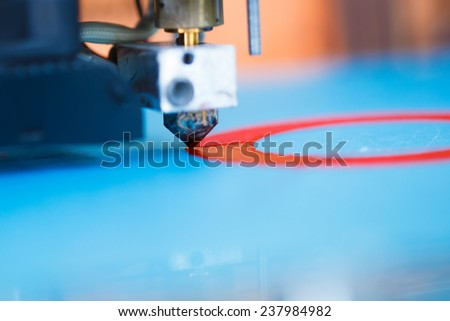 head of 3d printer in action, macro view - stock photo