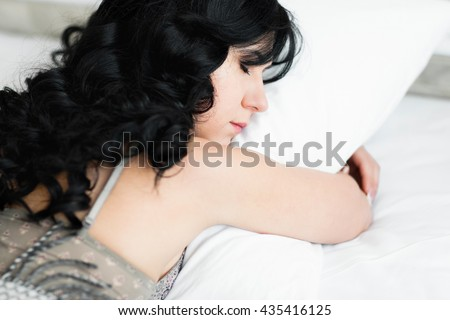 Head of sleeping girl hugging white pillow. Close-up of young attractive woman head and shoulders, who sleeps on stomach and hugs her pillow. Beautiful brunette woman hugs pillow
