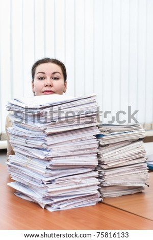 Head of young caucasian woman behind pile from project drawings blueprints