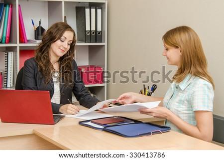 Head puts his signature on the document, the secretary sitting next - stock photo