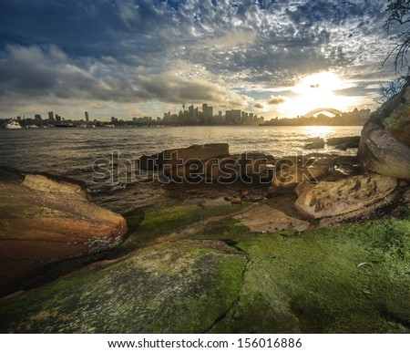 head reserve park around harbor at sunset with rocks in sea water on foreground panoramic cityscape - stock photo